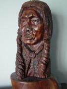 A Carved walnut bust of an aging brave with more years behind him than lie ahead.